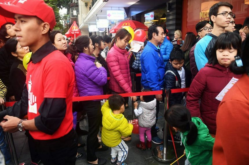 People queue up outside Hanoi's first McDonald's fast food chain restauranti on Dec 2, 2017.