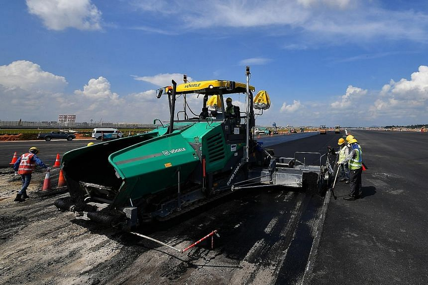 Workers paving a taxiway. It is forecast that Singapore's total air passenger traffic and the number of aviation-related jobs could more than double in 20 years.