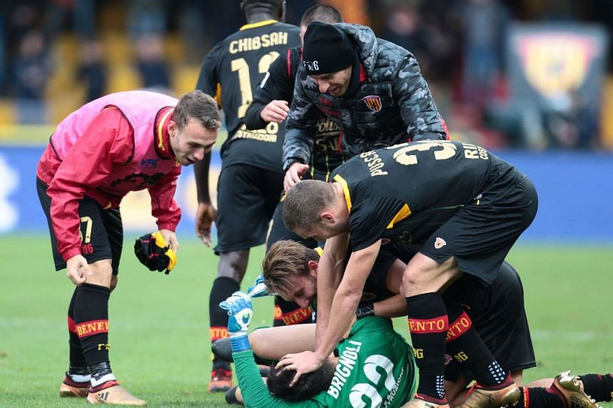 Benevento's Italian goalkeeper Alberto Brignoli is the toast of his team-mates after scoring a late equaliser for a 2-2 Serie A draw against AC Milan on Dec 3, 2017 at the Ciro Vigorito Stadium in Benevento.