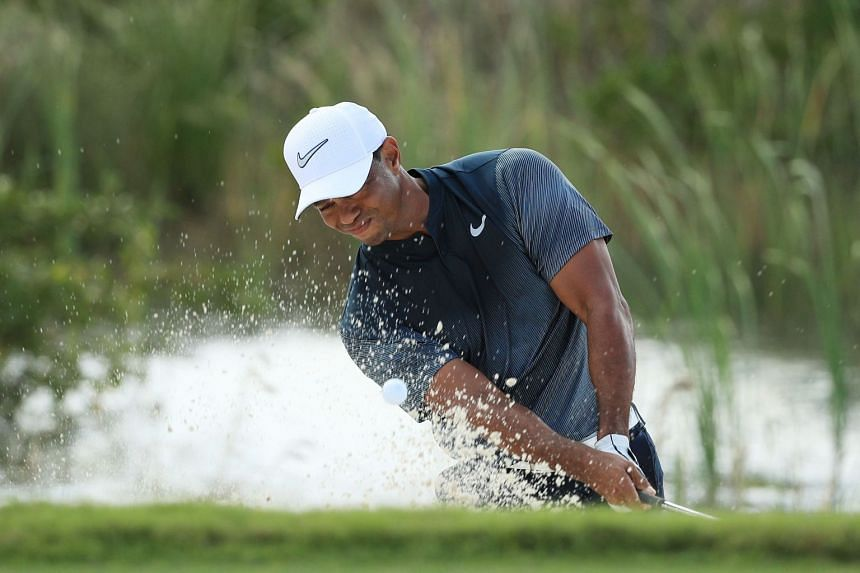 Woods plays a shot from a bunker on the fifth hole during the third round.