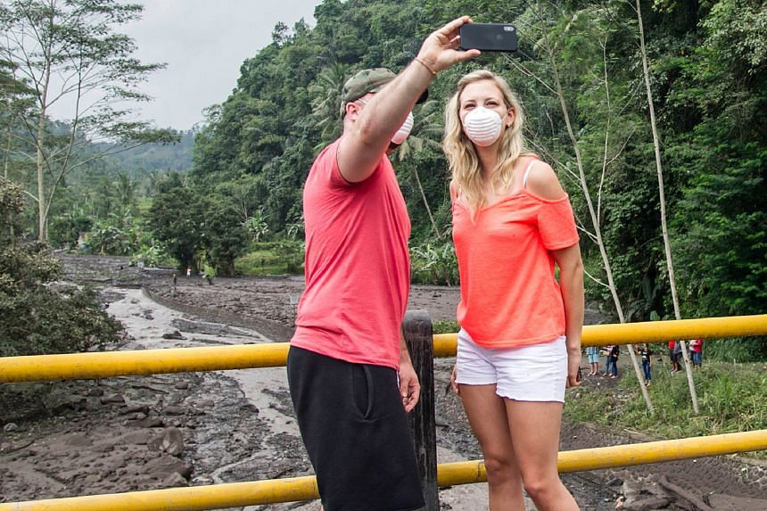 Tourists taking a selfie near the restricted area around Mount Agung in Karangasem, Bali, last Wednesday. Right: Typhoon Hato hit Hong Kong in August. But nasty weather is not keeping visitors away. Right, below: Residents evacuating their homes afte