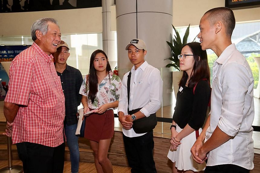 Dr Ng Eng Hen meeting Toa Payoh Central's Edusave award recipients, including poly graduate Zulhafiz Zulkifli (right).