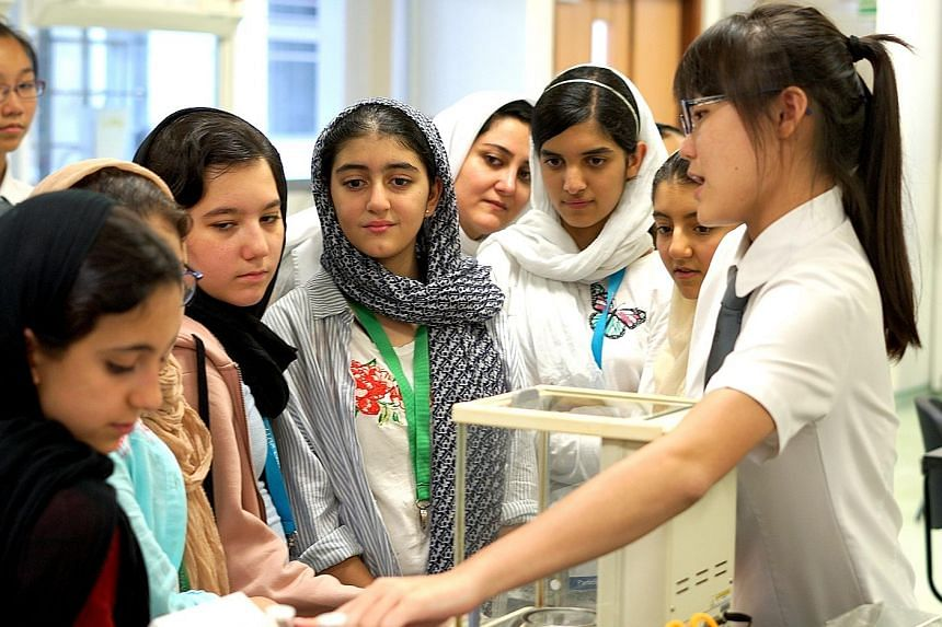 Team Singapore pupils testing out augmented reality on mobile devices during the Into The World experience at the ArtScience Museum. A student from the NUS High School of Mathematics and Science showing the girls from Team Iran how facilities in one