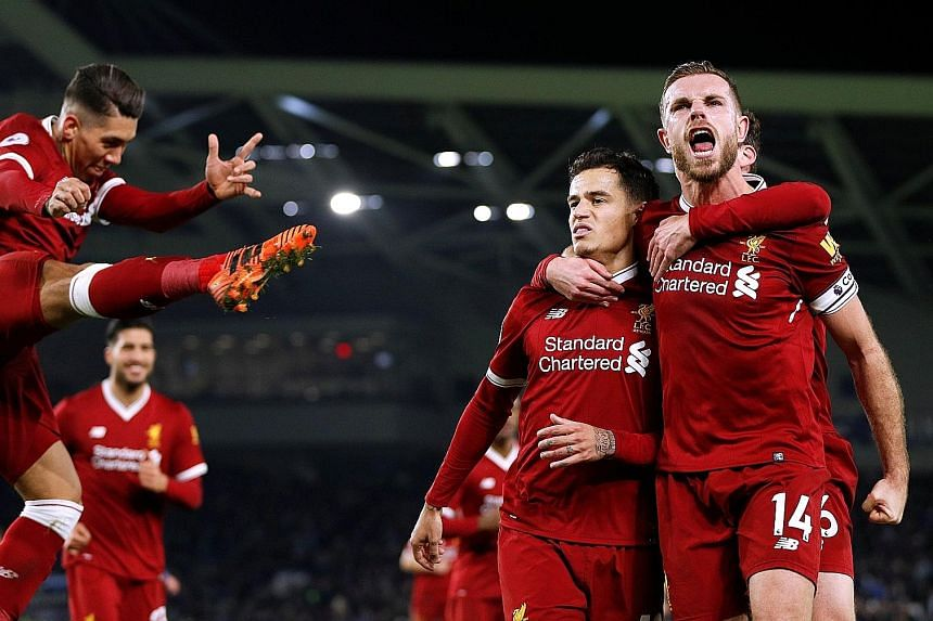 Liverpool's Philippe Coutinho celebrates scoring their fourth goal with captain Jordan Henderson as Roberto Firmino joins in.