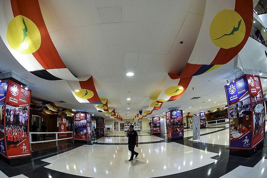 A worker putting the finishing touches to decorations for Umno's General Assembly to be held at the Putra World Trade Centre in Kuala Lumpur this week. The reception area (below) of he Putra World Trade Centre decorated with Umno flags. Umno secretar