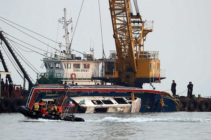 The capsized Seonchang-1 fishing boat being lifted out of the water during a salvage operation in the sea off Incheon, South Korea, yesterday. It collided with a 336-tonne fuel tanker yesterday morning.