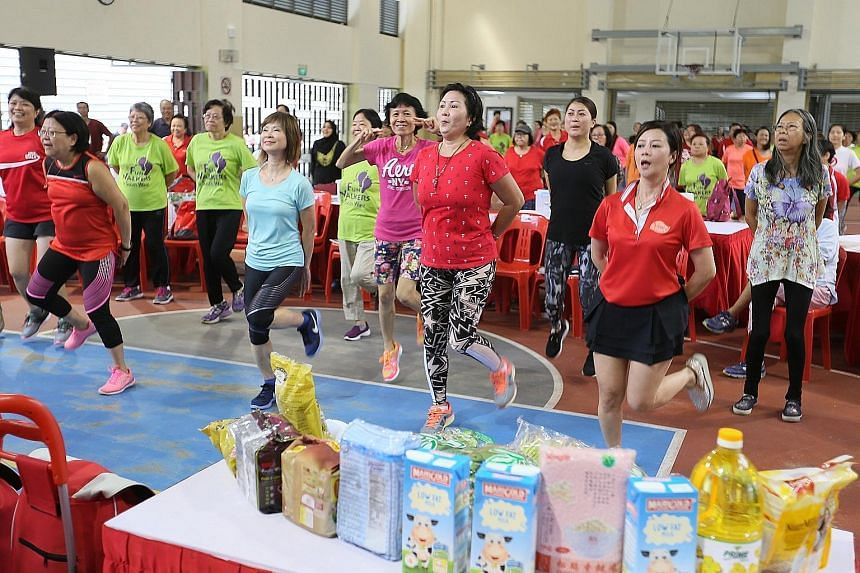 Senior Minister of State Amy Khor (in blue) and Hong Kah North residents performing a series of exercises at the Hong Kah North Community Club yesterday.