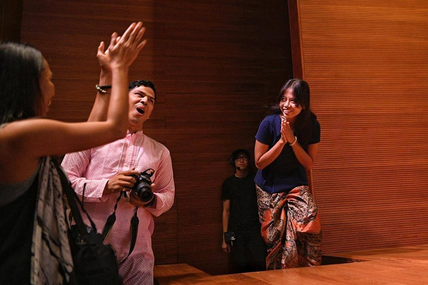 Indonesian domestic worker Deni Apriyani walks up the stage to receive her award during the annual Migrant Worker Poetry Competition on Dec 3.