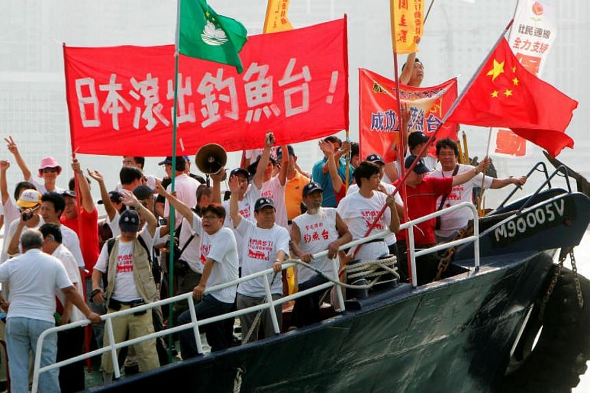 Activists shout slogans and wave the Chinese flag aboard a vessel in Hong Kong on Oct 22, 2006. Japan and China have sparred over a group of uninhabited islands known as the Senkaku islands in Japan and the Diaoyu islands in China.