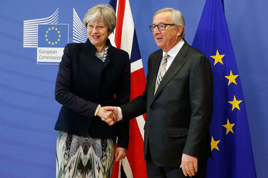 British PM Theresa May is welcomed by EU Commissioner President Jean-Claude Juncker ahead of a meeting in Brussels on Dec 4, 2017. Britain has made an agreement to keep economic rules on both sides of the border in Ireland similar enough to allow no