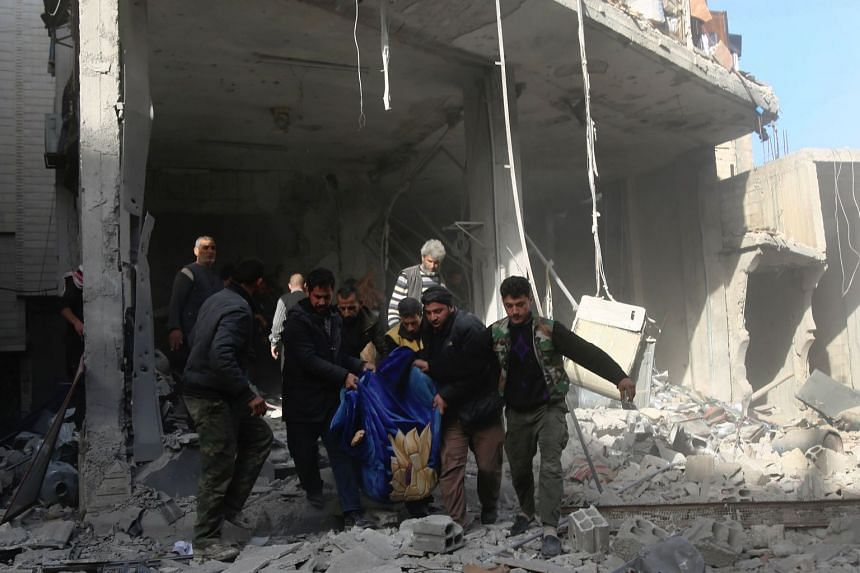 Syrians carrying a victim following a reported air strike on the town of Hammuriyeh, near Damascus, on Dec 3, 2017.