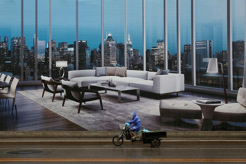 A man rides a tricycle past an advertising poster for luxury apartments in Beijing on July 19, 2016.