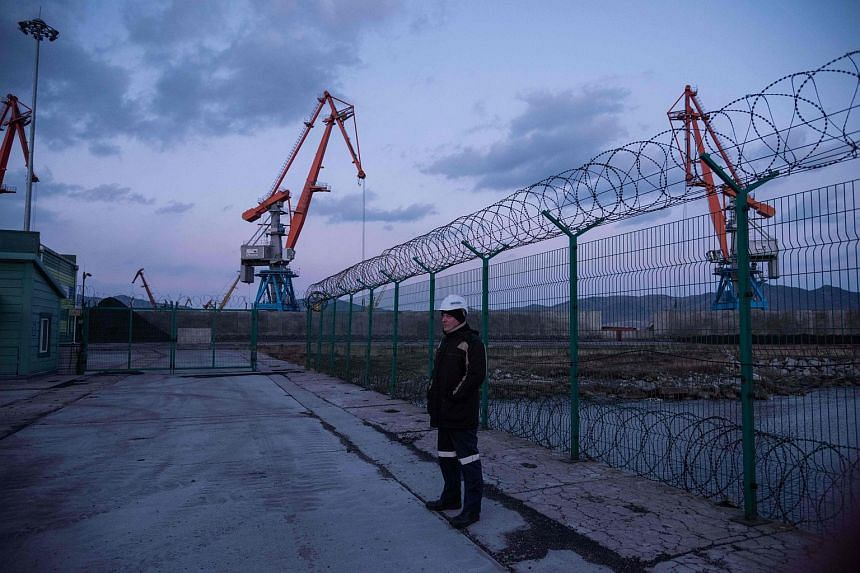 A Russian worker standing before a fence at the RasonConTrans coal port at Rajin harbour in the Rason Special Economic Zone.