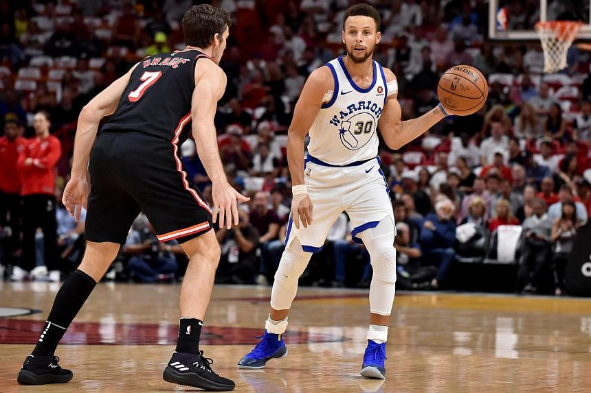 Golden State Warriors guard Stephen Curry (30) is guarded buy Miami Heat guard Goran Dragic (7) during the first half at American Airlines Arena.