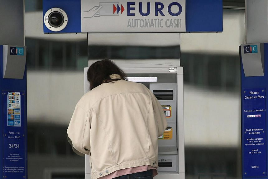 A customer uses an ATM machine at a bank branch of French bank Credit Industriel et Commercial (CIC) in Nantes, France.