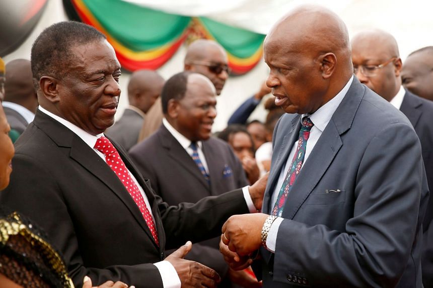 Zimbabwean President Emmerson Mnangagwa congratulates his Minister of Finance, Patrick Chinamasa after the swearing in of cabinet ministers at State House in Harare, on Dec 4, 2017.