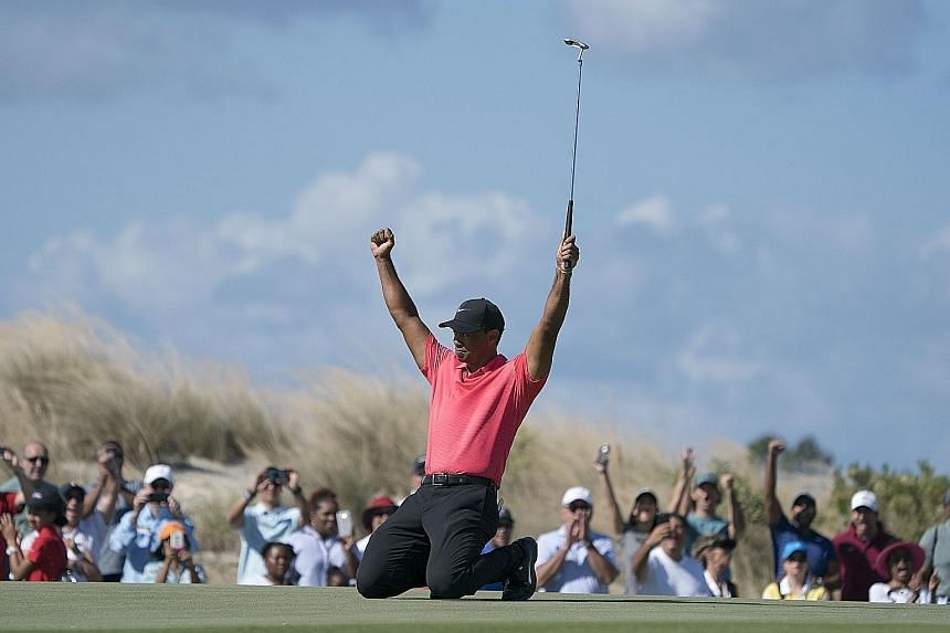 Tiger Woods celebrating after making his eagle putt on the seventh hole during the final round of the Hero World Challenge at Albany Golf Club, much to the delight of the crowd. The 41-year-old completed his first tournament in 12 months following ye