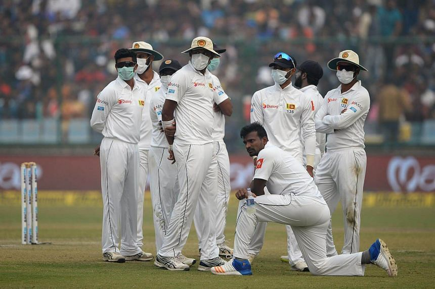 Sri Lanka cricket players wear masks in an attempt to protect themselves from air pollution during the second day of the third Test cricket match between India and Sri Lanka at the Feroz Shah Kotla Cricket Stadium in New Delhi on Dec 3, 2017.