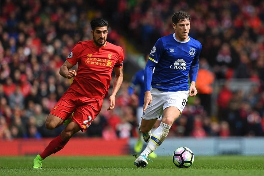 Everton's English midfielder Ross Barkley vies with Liverpool's German midfielder Emre Can during the English Premier League football match between Liverpool and Everton at Anfield in Liverpool on April 1, 2017.