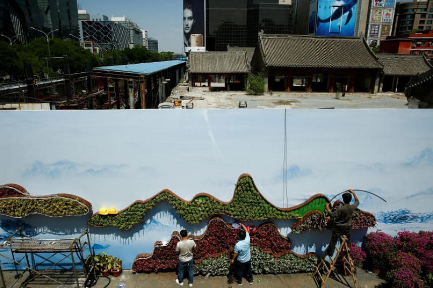Workers set up a flower display ahead of the the Belt and Road Forum in Beijing on May 10, 2017.