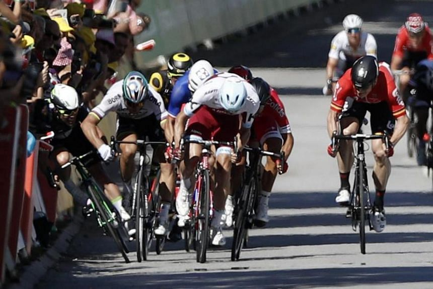A file picture dated July 4, 2017 shows Bora Hansgrohe team rider Peter Sagan (second left) of Slovakia pushing Team Dimension Data rider Mark Cavendish (left) of Britain during the final sprint of the 4th stage of the Tour de France cycling race.