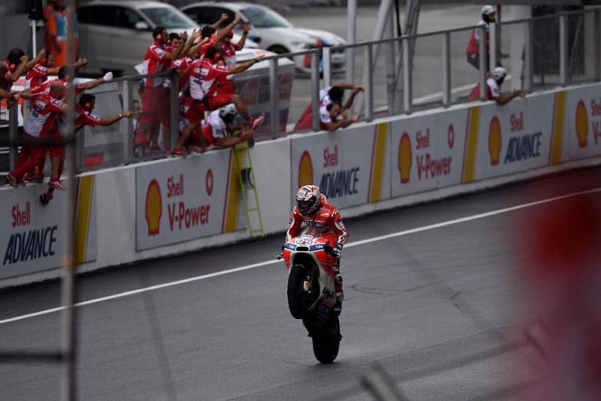 Ducati's Italian rider Andrea Dovizioso does a wheelie after winning the Malaysia MotoGP at the Sepang International circuit in Sepang on Oct 29, 2017.