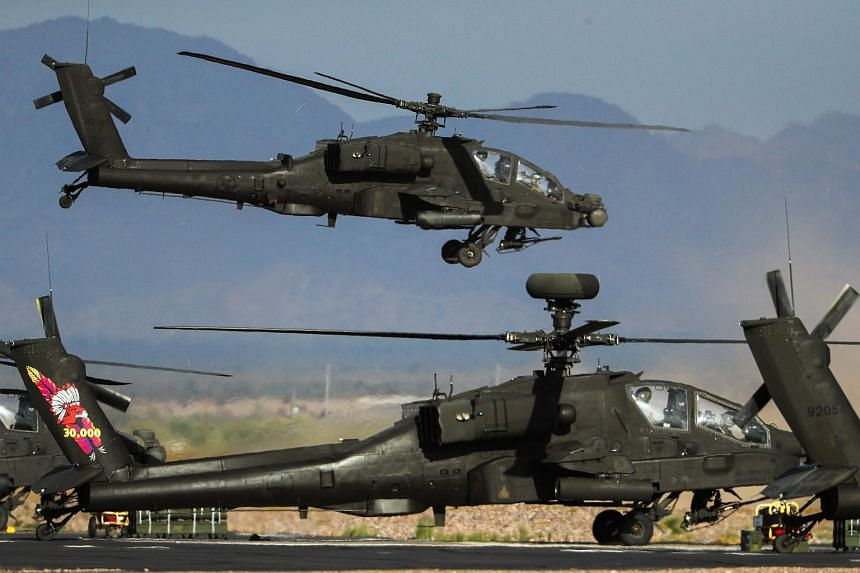 Apache attack helicopters taking off from Gila Bend Air Base to head to the live-fire range during Exercise Forging Sabre.