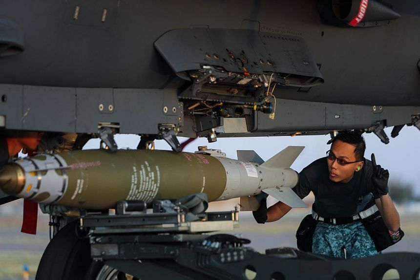 An Air Force engineer checking a bomb that has been mounted on an F-15 fighter, during Exercise Forging Sabre.