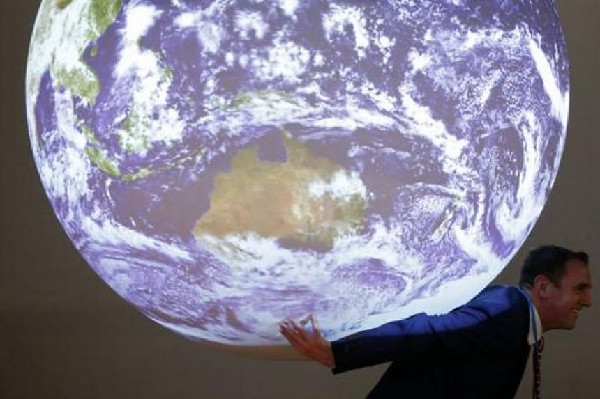 A participant poses with a replica of the planet during the World Climate Change Conference 2015 (COP21) at Le Bourget, near Paris, France, on Dec 8, 2015.