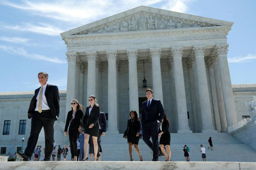 People walk out after the US Supreme Court granted parts of the Trump administration's emergency request to put his travel ban into effect immediately, on June 26.