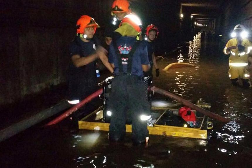 Singapore Civil Defence Force (SCDF) officers working to clear water in the flooded MRT tunnel on Oct 8.