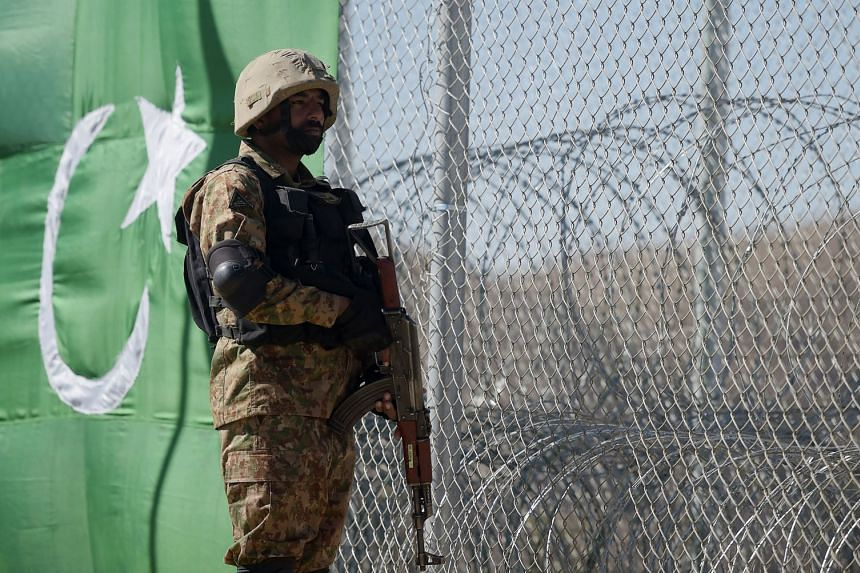 A Pakistani soldier keeps vigil next to a newly fenced border between Pakistan and Afghanistan on Oct 18, 2017.
