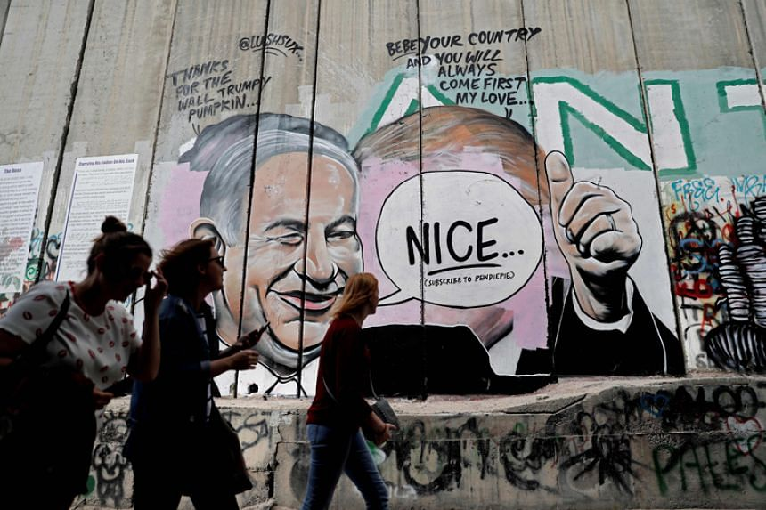 A graffiti by street artist Lushsux, that originally depicted US President Donald Trump kissing Israeli Prime Minister Benjamin Netanyahu, is seen after it was painted over and then reworked on by the artist on the controversial Israeli separation wa
