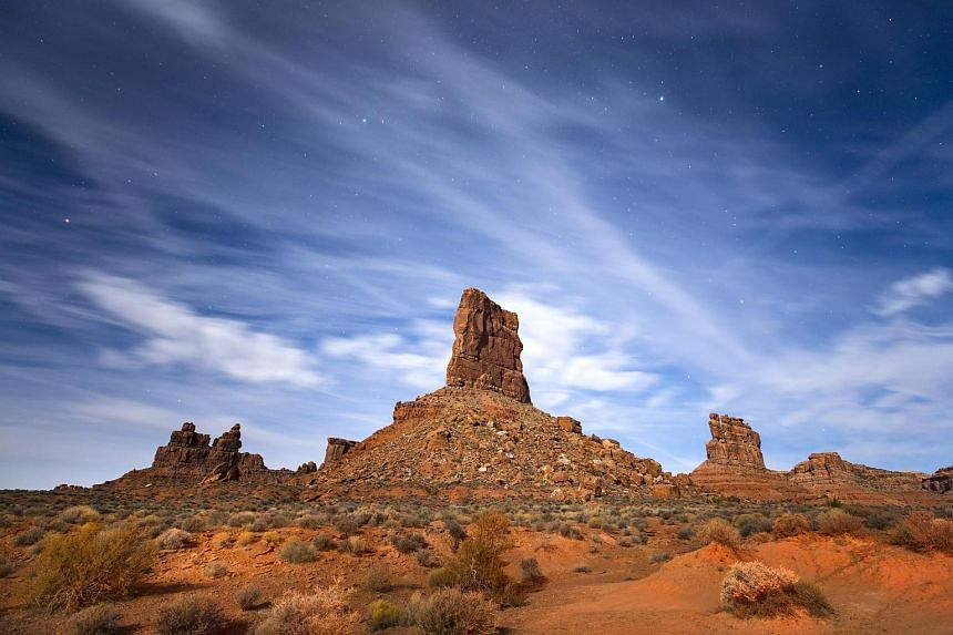 Sandstone buttes rise from the Valley of the Gods under a full moon in Bears Ears National Monument near Mexican Hat, Utah.