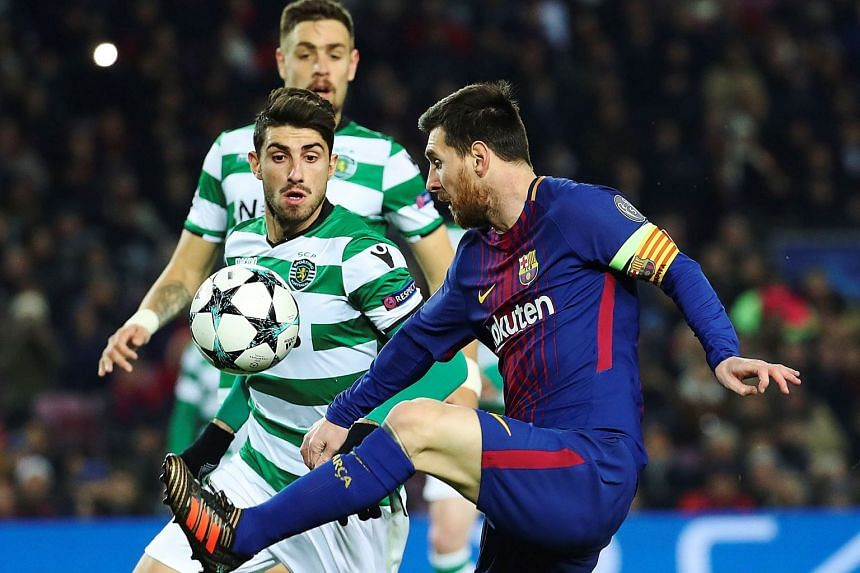 Barcelona's Argentinian striker Leo Messi (right) vies for the ball with Sporting Lisbon's Cristiano Piccini.