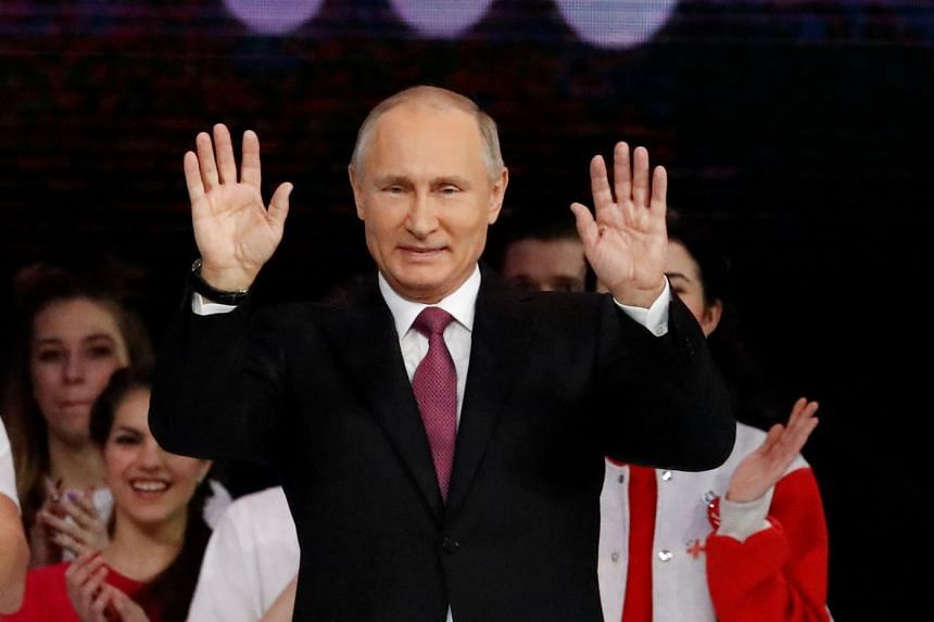Vladimir Putin greets the audience at the congress of volunteers in Moscow, Dec 6, 2017.