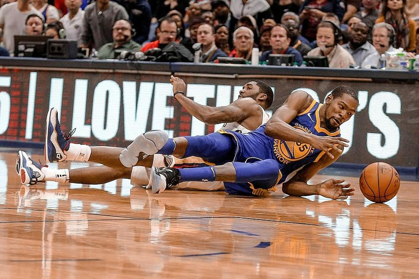 Golden State forward Kevin Durant (right) and New Orleans guard E'Twaun Moore scramble for a loose ball. Durant was later thrown out of the game, which the Warriors won 125-115 after fighting back from 21 points down.