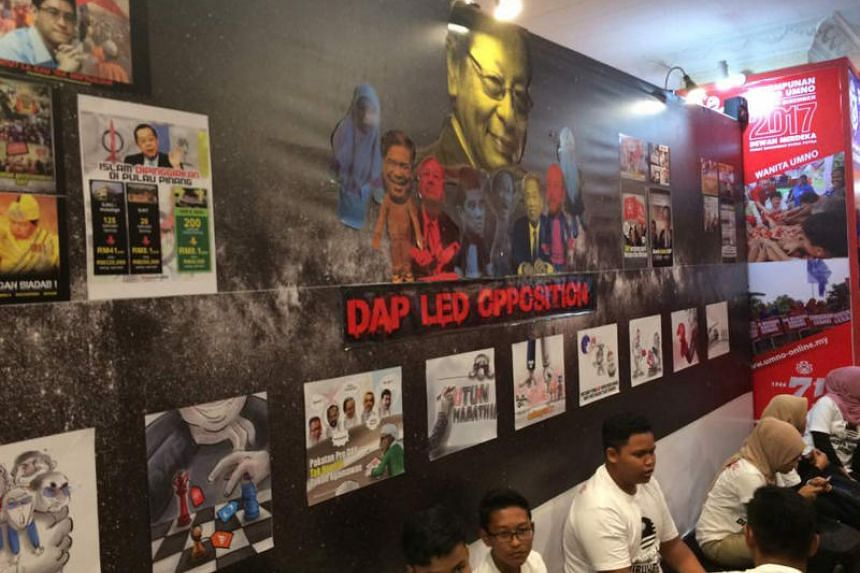 Umno puts up posters and drawings to belittle the DAP and other opposition parties on a wall at its annual assembly in Kuala Lumpur, on Dec 6, 2017.