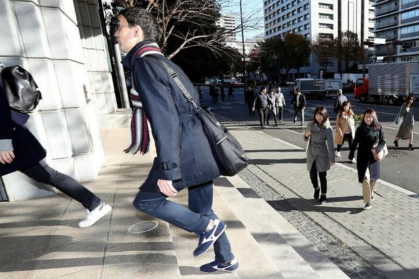 Officials from the Japan Sports Agency wear sneakers on their way to the office in Tokyo on Dec 6, 2017.