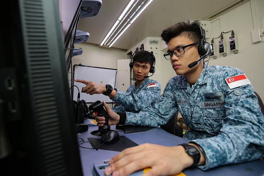 Second Lieutenant Luis Lo (right) a Heron 1 UAV pilot, receiving instructions from Captain Ronald Lim, the pilot in command, during Exercise Forging Sabre.