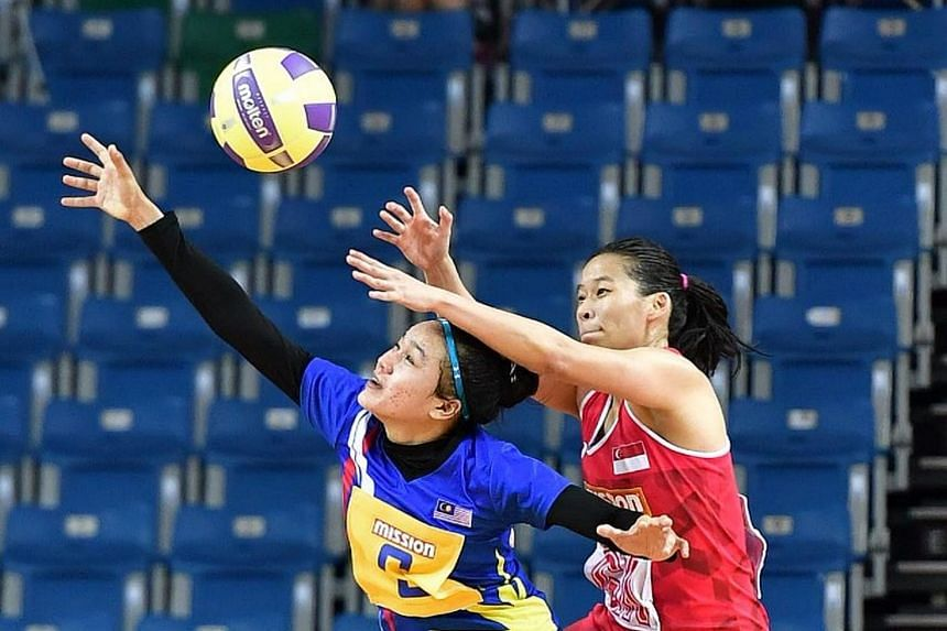 Singapore GK Melody Teo (in red) defending against Malaysia's Noor Haidayu Hasmira Hasbullah during their Nations Cup match on Dec 6, 2017.