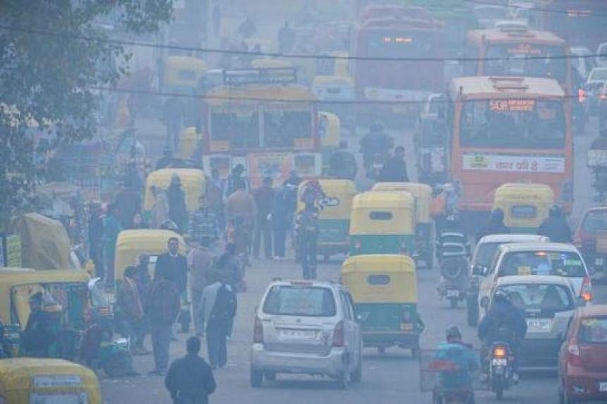 Indian commuters travel on a polluted road near a bus terminus in the Anand Vihar District of New Delhi on Dec 18, 2015.