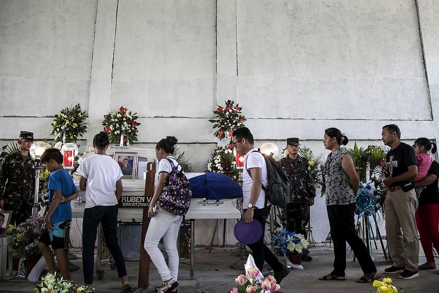 Mourners paying their respects to murdered environmental para-enforcer Ruben Arzaga, in El Nido, Palawan island, the Philippines, on Sept 28.
