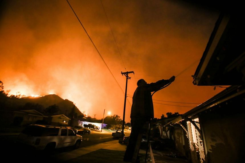 A man waters his home as firefighters battle a wildfire near homes in Santa Paula, California.