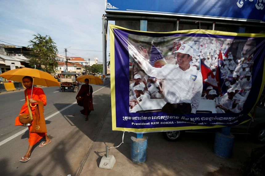 Buddhist monks walk past a banner of opposition leader Kem Sokha at the Cambodia National Rescue Party   headquarters in Phnom Penh, Cambodia.