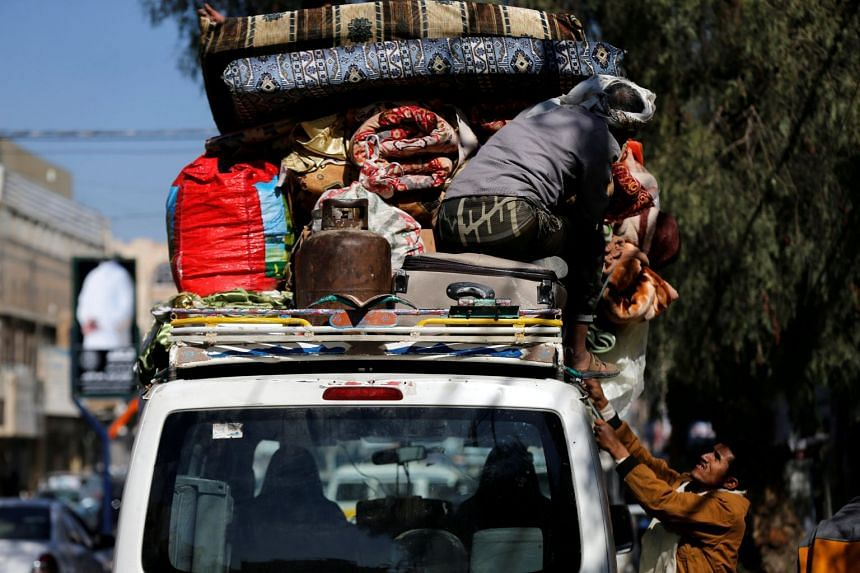People load belongings on a van as they evacuate their house located on a street where Houthis have recently clashed with forces loyal to slain Yemeni former president Ali Abdullah Saleh in Sanaa, Dec 6, 2017.