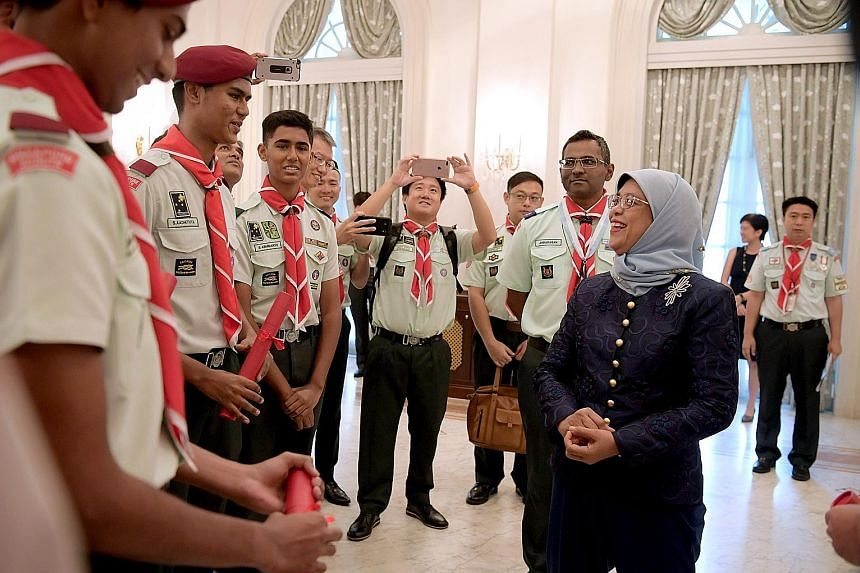 President Halimah Yacob chatting with scouts after an investiture ceremony held at the Istana yesterday. During the ceremony, Madam Halimah was welcomed as the patron of the Girl Guides Singapore and the Singapore Scout Association. She also presente