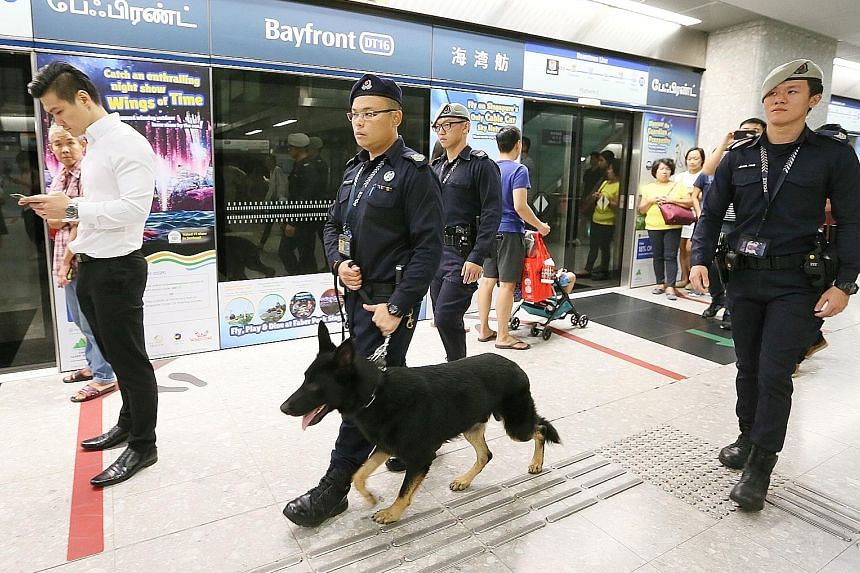Senior Staff Sergeant Wong Wenxiong with his dog Esso and Sergeant (NS) Bryant Choo patrolling at Bayfront MRT station. Police dogs are leashed and will not approach a person without a command from their handler.