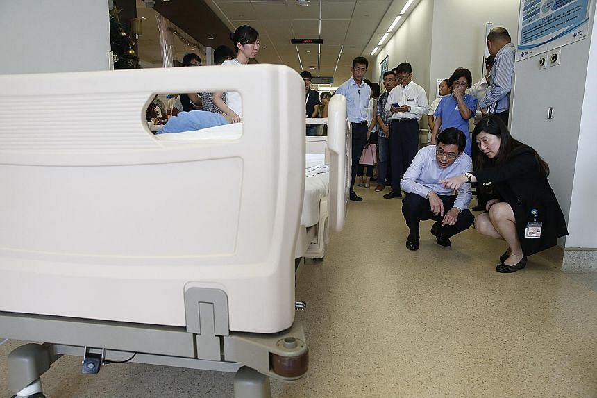 Finance Minister Heng Swee Keat being shown a bed transporter at Changi General Hospital. The innovation makes it easier to move beds with patients lying on them, and cuts the risk of staff getting injured on the job.