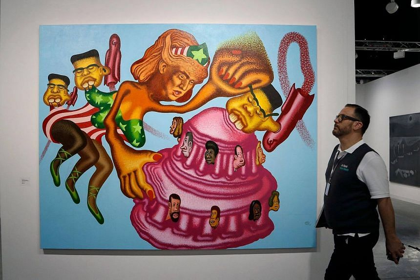 A patron walks past 'President Trump Becomes a Wonder Woman, Unifies the Country and Fights Rocket Man' By American artist Peter Saul during the Art Basel Miami in Miami, Florida.